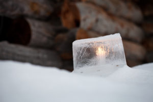 Ice lantern with white candle burning inside