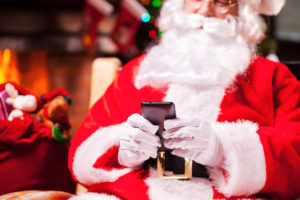 Santa Claus texting. Close-up of Happy Santa Claus typing message on the mobile phone and smiling while sitting at his chair